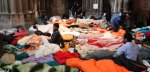 Refugees sit in a mattress camp in Votivkirche church in Vienna